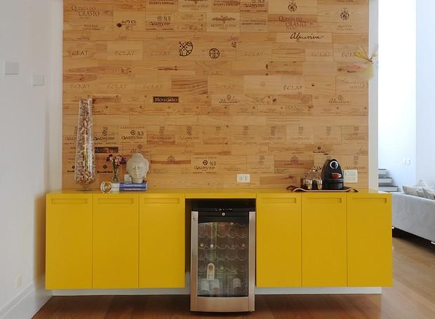 O bufê amarelo com desenho da arquiteta Luita Trench ganha destaque na frente da parede feita com caixas de vinho (Foto: Marcelo Magnani/Casa e Jardim)