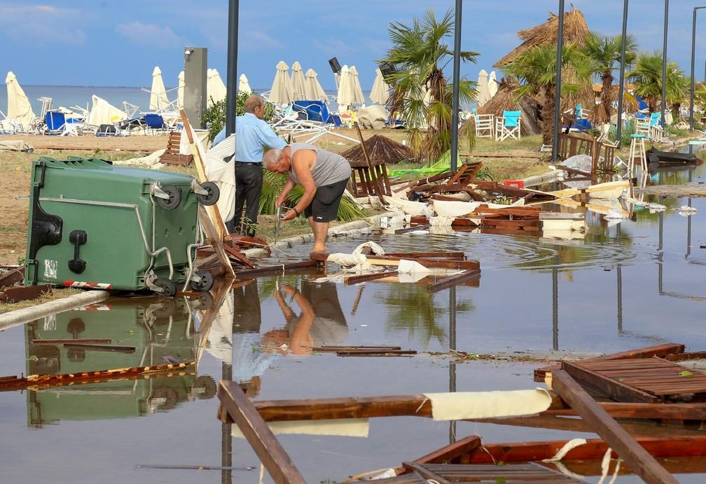Homens fazem buscas nesta quinta-feira (11) nos destroços deixados pela forte tempestade que atingiu a região de Halkidiki, no norte da Grécia  — Foto: Giannis Moisiadis / InTime News via AP