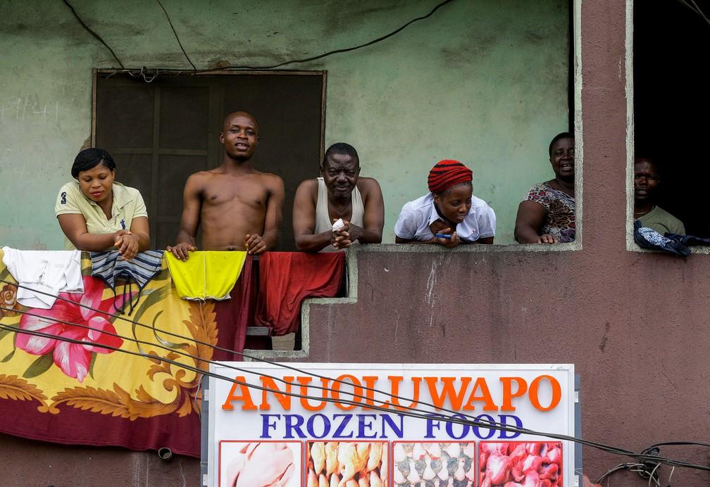 Moradores de um prédio olham da varanda em Lagos, na Nigéria, em 31 de março, enquanto a cidade enfrenta um bloqueio de duas semanas com os moradores instruídos a ficarem em suas casas para impedir a propagação do novo coronavírus — Foto: Sunday Alamba/AP