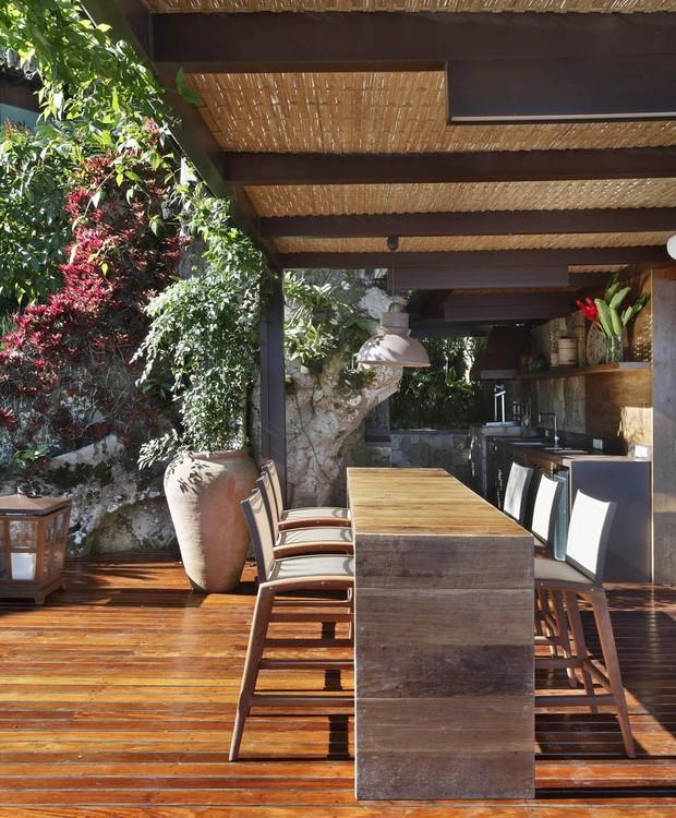 O espaço gourmet da área externa recebeu um forro de palhinha sob a cobertura de vidro, para suavizar o calor do sol  (Foto: Juliano Colodeti/MCA Estúdio/Divulgação)