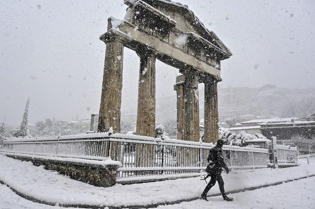 Pedestre passa diante da Ágora Romana de Atenas, na Grécia, coberta de neve durante forte nevasca — Foto: Louisa Gouliamaki/AFP