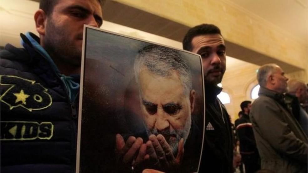 Simpatizantes do Hezbollah seguram cartaz em homenagem a Soleimani, que ajudou a financiar milícias que agora podem alvejar americanos — Foto: AFP