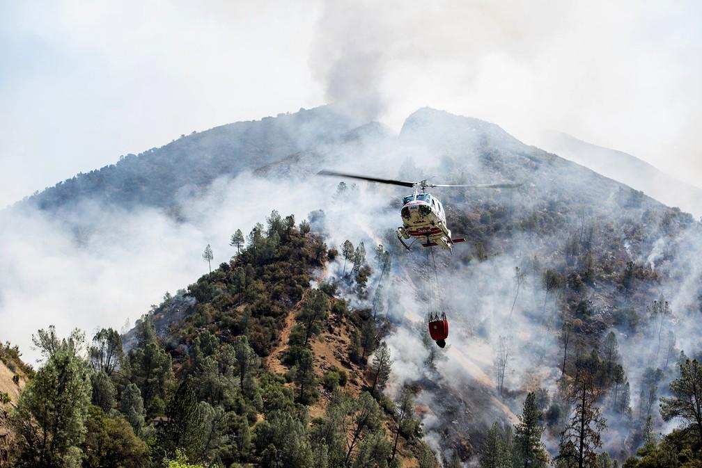 Helicóptero tenta combater as chamas em incêndio próximo ao parque Yosemite, na Califórnia (Estados Unidos) (Foto: Andrew Kuhn /The Merced Sun-Star via AP)
