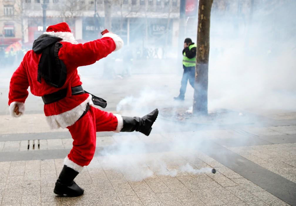 Manifestante vestido de Papai Noel chuta bomba de gás lacrimogêneo em Paris, França — Foto: Gonzalo Fuentes/Reuters