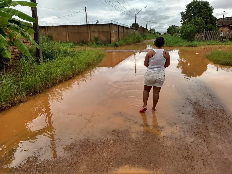 Moradora Aline Santos enfrentou água quase no joelho ao sair de casa para comprar pão no bairro Lagoa. — Foto: Diêgo Holanda/G1