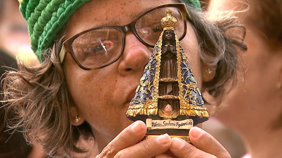 Fiel ora com imagem de Nossa Senhora Aparecida nas mãos em Ribeirão Preto — Foto: Fábio Junior/EPTV