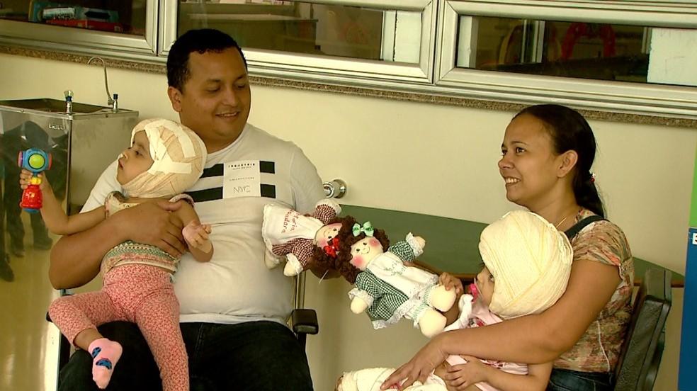 Com as filhas no colo, Diego e Débora Freitas seguram as 'bonecas siamesas' em Ribeirão Preto — Foto: Cláudio Oliveira/EPTV