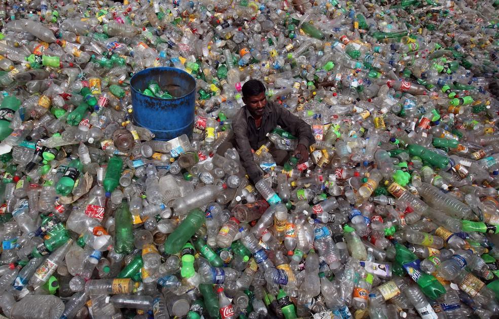 Um homem separa garrafas em um aterro de itens de plástico durante o Dia Mundial do Meio Ambiente em Chandigarh, na Índia. — Foto: Ajay Verma/Reuters