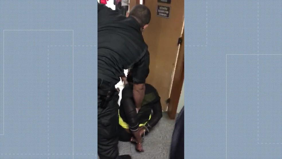 Imagens mostram a advogada Valéria dos Santos no chão, algemada por policiais (Foto: Reprodução/ TV Globo)
