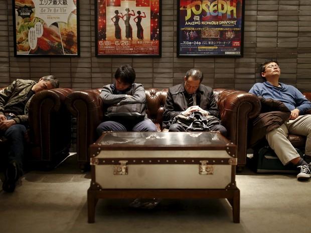Homens dormem no sofá de uma loja de Tóquio  (Foto: Thomas Peter/Reuters)