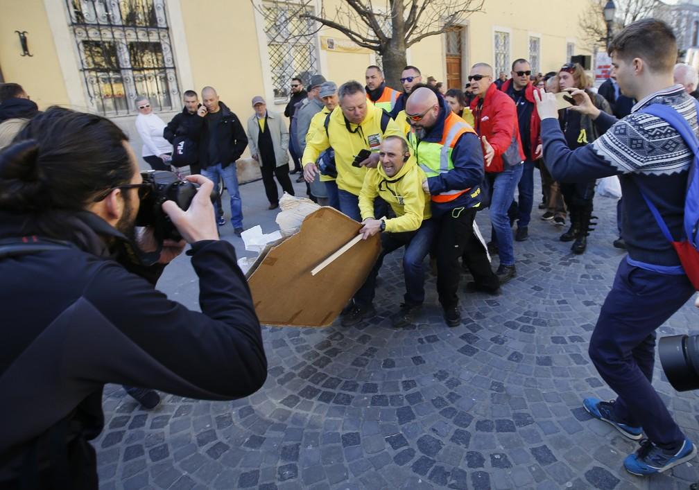 """Manifestante com um cartaz que afirma """"Não há liberdade de discurso nesse país"""" é detido pela polícia durante comício do premiê Viktor Orban em Szekesfehervar (Foto: Darko Vojinovic/AP Photo)"""