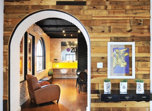 A parede de entrada foi feita com madeiras de paletes e caixas de feiras. Elas receberam verniz mais escuro para parecer madeira de demolição (Foto: Sidney Doll)