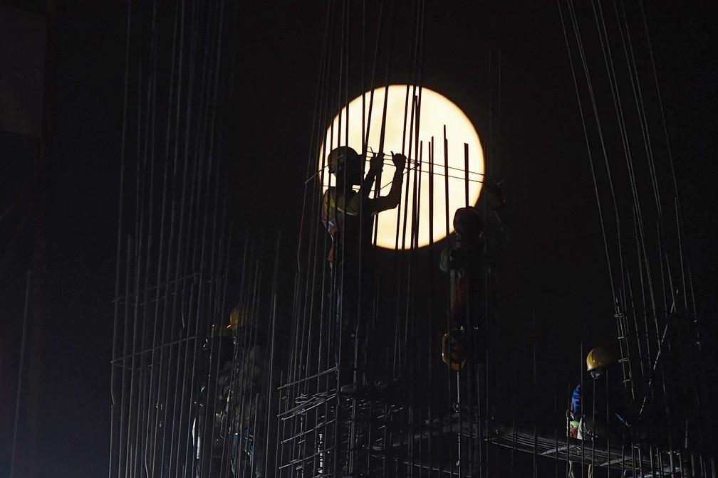 Superlua é vista enquanto indianos trabalham em um canteiro de obras em Calcutá — Foto: Dibyangshu Sarkar/AFP
