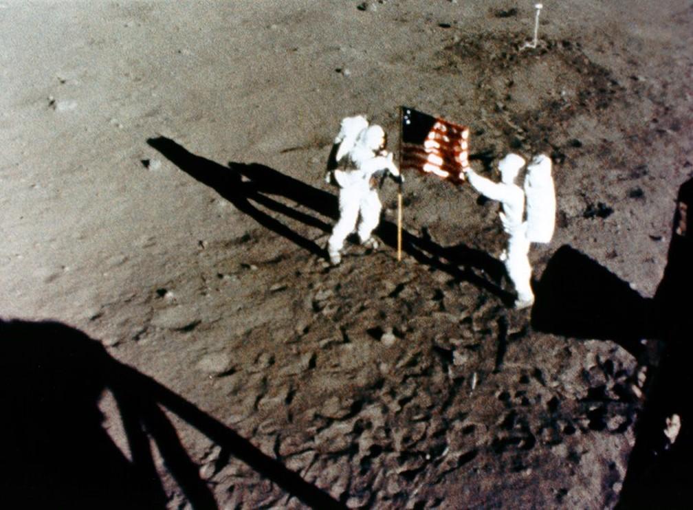 Reprodução do frame de uma câmara 16-mm mostra Neil (esq.) e Buzz (dir.) fincando a bandeira dos EUA — Foto: Divulgação/Nasa