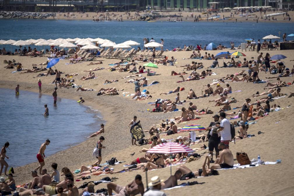 Pessoas tomam banho de sol em praia em Barcelona, na Espanha, na terça-feira (8) — Foto: Emilio Morenatti/AP