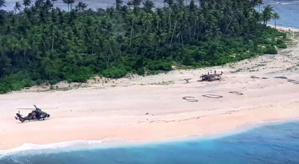 Homens foram resgatados após escreverem SOS na areia — Foto: Reuters