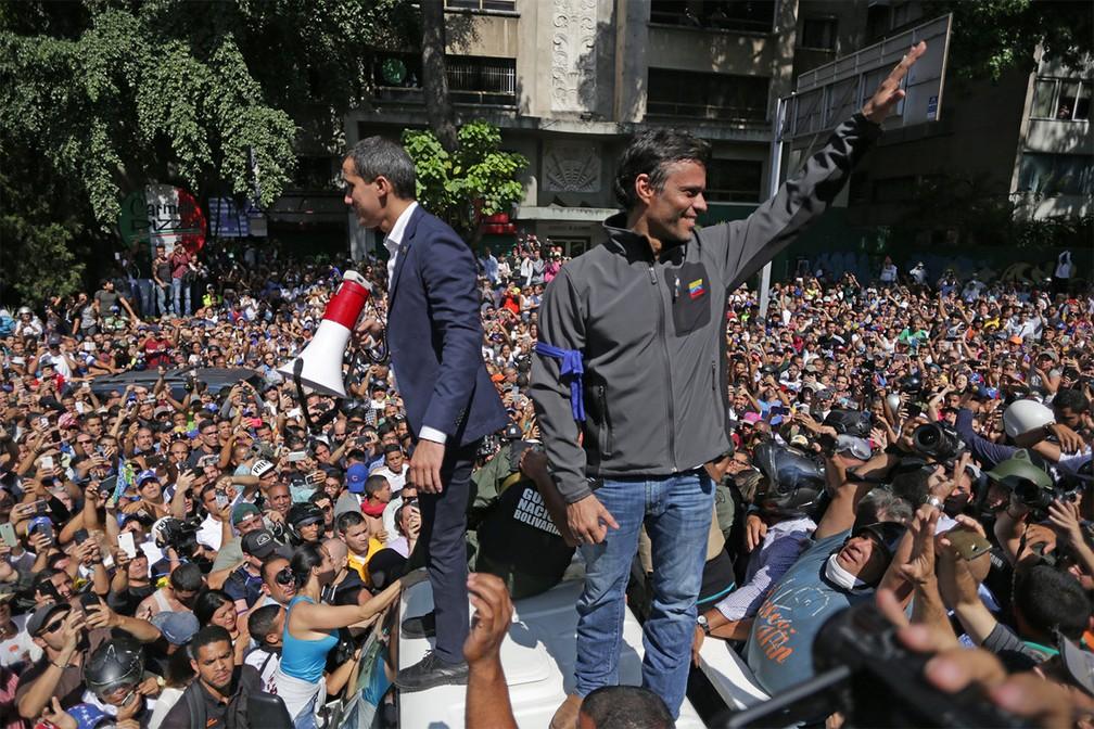 Ao lado de Leopoldo López, Juan Guaidó fala a multidão de cima de um carro em Caracas, após convocar o povo às ruas contra Maduro — Foto: Cristian Hernández/AFP