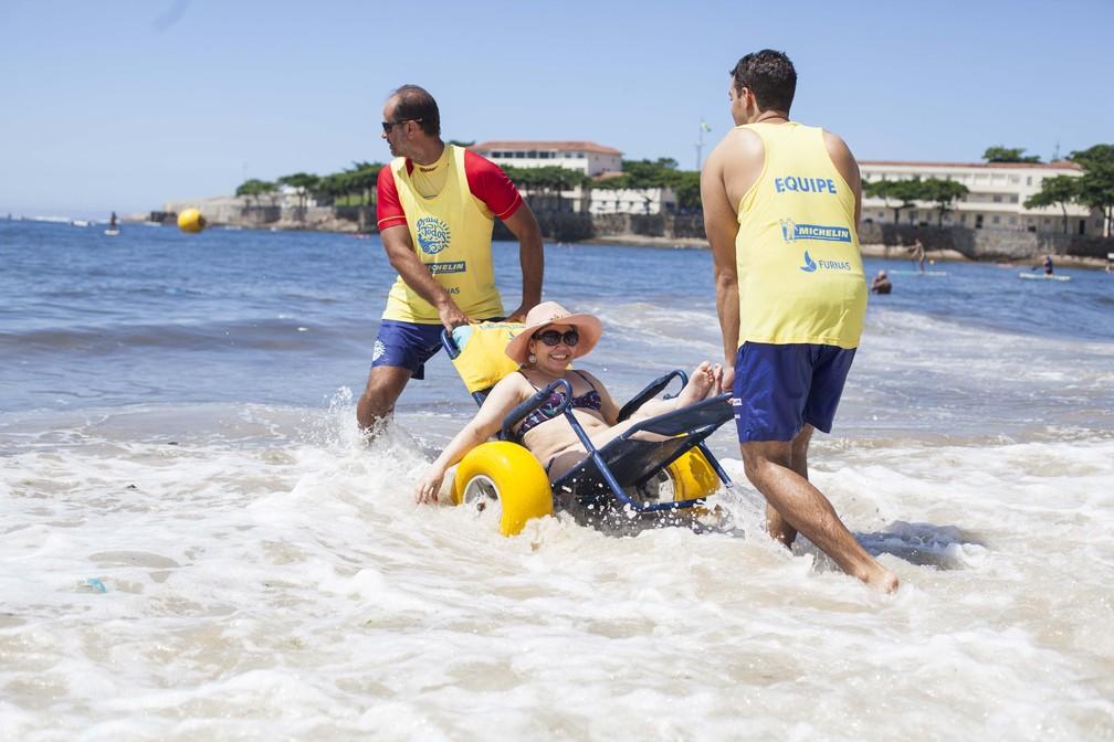 Cadeirante Laura Martins entrando no mar de Copacabana, no Rio de Janeiro, com a ajuda de voluntários da ONG Praia para Todos — Foto: Arquivo pessoal/Laura Martins