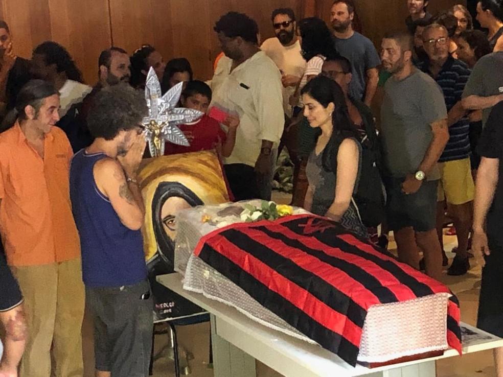 Letícia Sabatella ao lado do caixão de Yuka, coberto por uma bandeira do Flamengo — Foto: Carlos Brito/G1