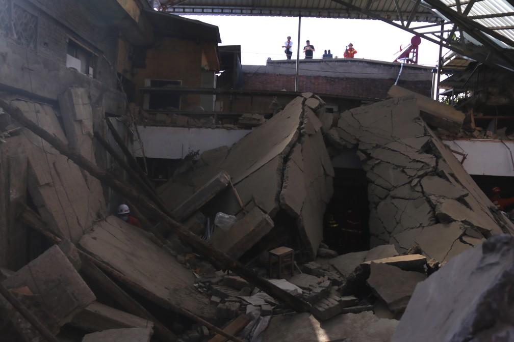 Socorristas procuram por sobreviventes de restaurante que desabou na província de Shanxi, na China, neste sábado (29) — Foto: Chinatopix Via AP