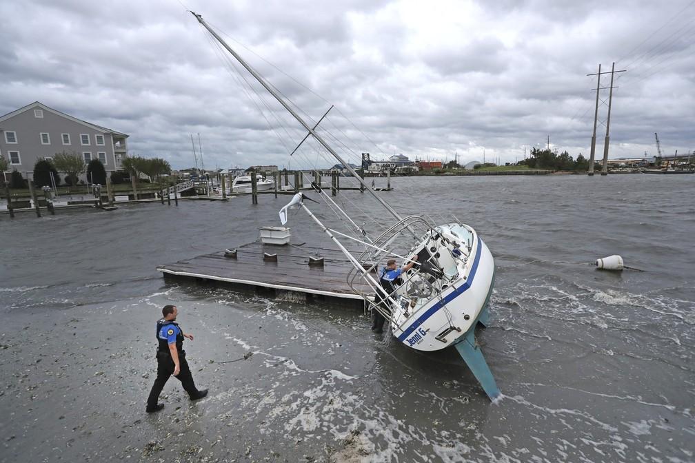 Policiais fazem vistoria em barco a vela em busca de ocupantes depois de o furacão Dorian passar pela costa da Carolina do Norte, nos Estados Unidos, nesta sexta-feira (6). — Foto: Tom Copeland/AP