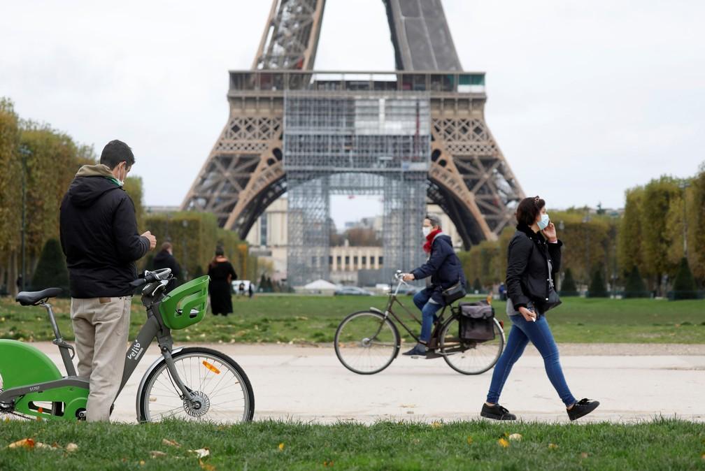 Pessoas caminham em Paris, na França, diante da Torre Eiffel, nesta quinta-feira (29), véspera da entrada em vigor de um novo lockdown — Foto: Charles Platiau/Reuters