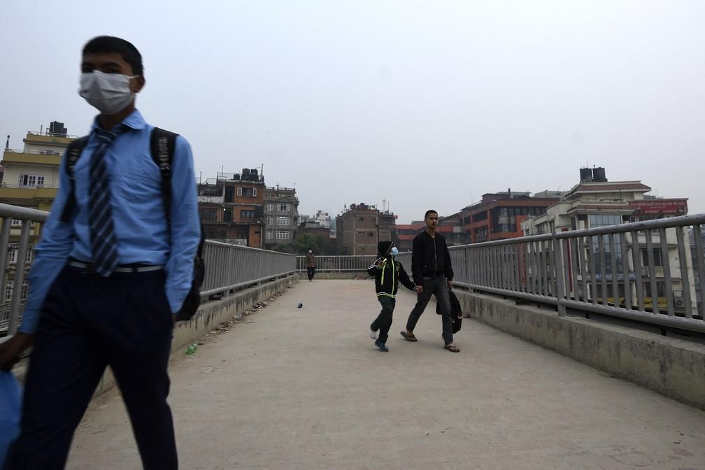 Jovem caminha em ruas de Katmandu, capital do Nepal, em segunda-feira (29) de nuvem de poluição histórica — Foto: Prakash Mathema/AFP