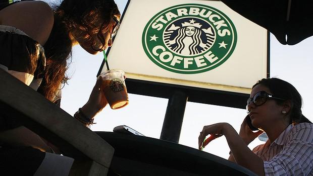 Clientes sentados em mesas diante de loja do Starbucks (Foto: Getty Images)