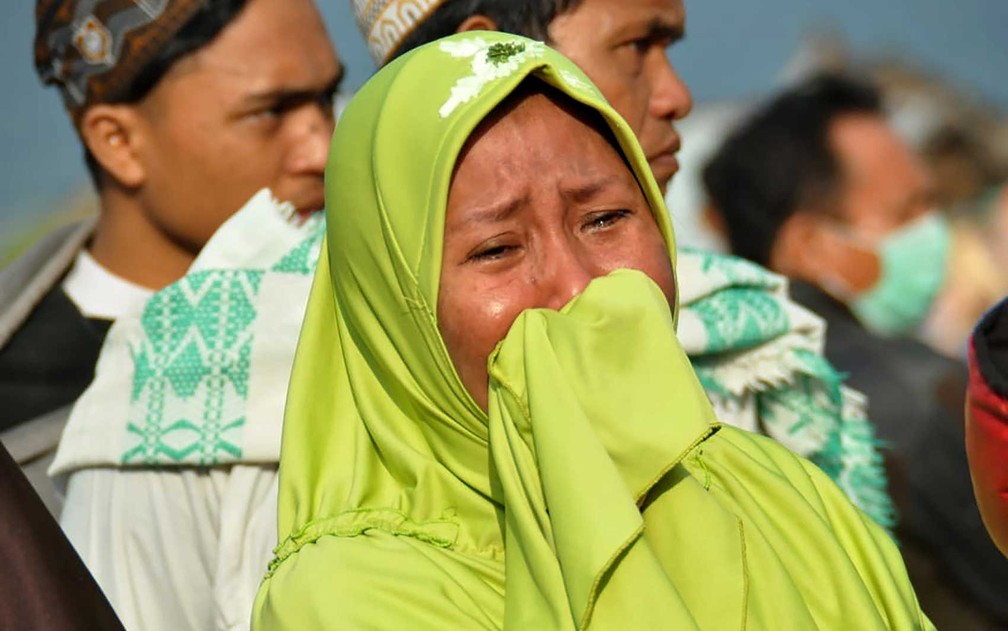 Mulher chora enquanto pessoas olham para os danos após terremoto e tsunami atingiram Palu, na ilha de Sulawesi — Foto: Muhammad Rifki / AFP