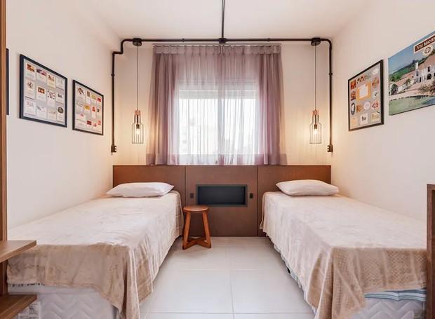 Duas camas de solteiro formam um segundo quarto. As luzes pendentes brincam com diferentes formas de iluminação e rementem à temática (Foto: Airbnb/ Reprodução)