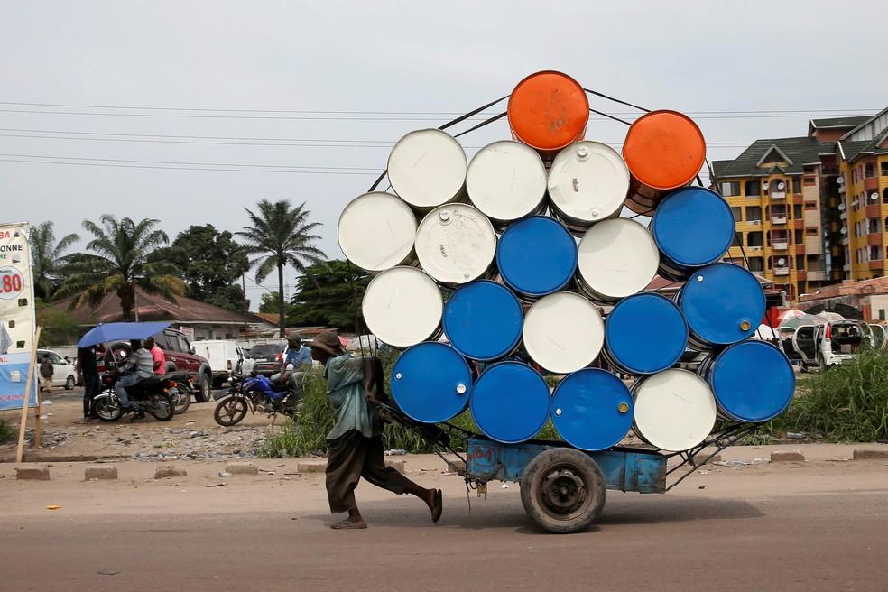 Um homem puxa uma carroça com barris em Kinshasa, na República Democrática do Congo, em dezembro de 2018 — Foto: Baz Ratner/Reuters