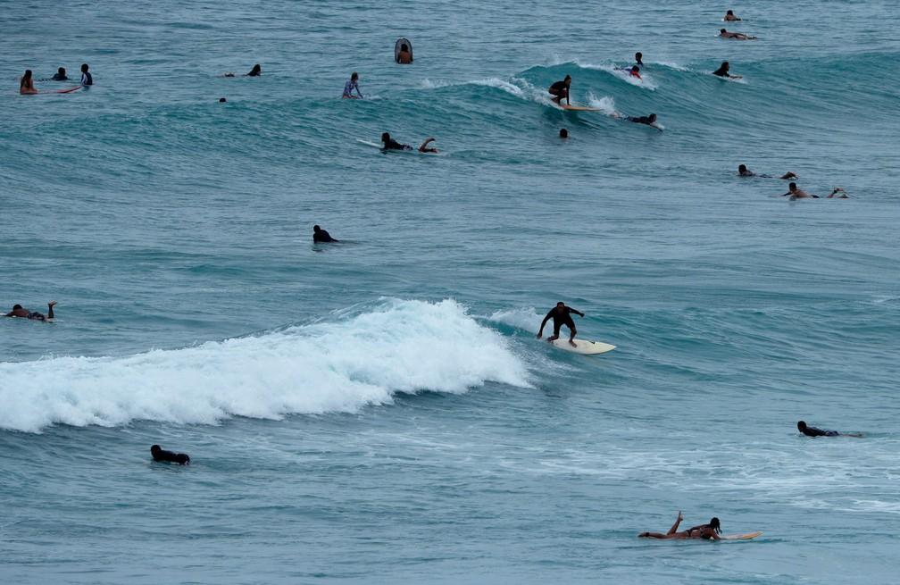 Surfistas aproveitam mar agitado para surfar na praia Waikiki, em Honolulu, no Havaí, na quinta-feira (23)  (Foto: John Locher/AP )