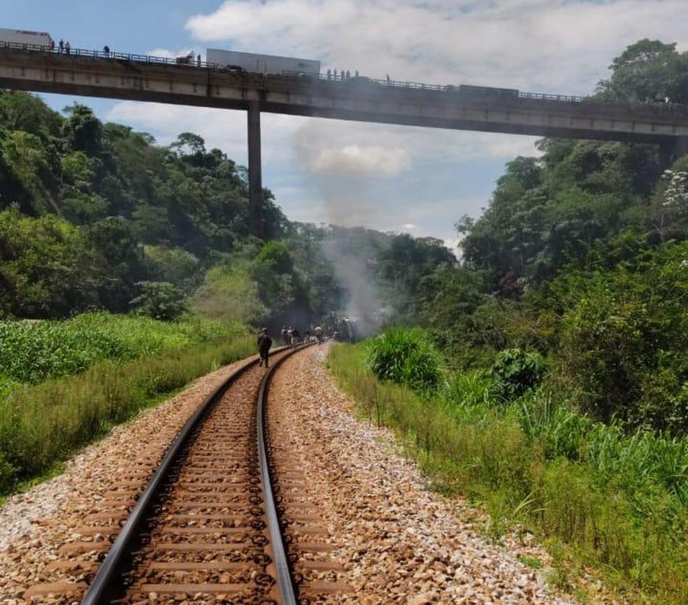 Do alto do viaduto pessoas olham para o ônibus que caiu de uma altura de 15 metros perto de uma linha férrea.  — Foto: Redes sociais