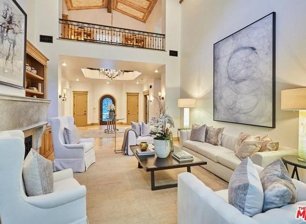 O hall de entrada está ligado a uma sala de estar com lareira (Foto: The MLS/ Reprodução)