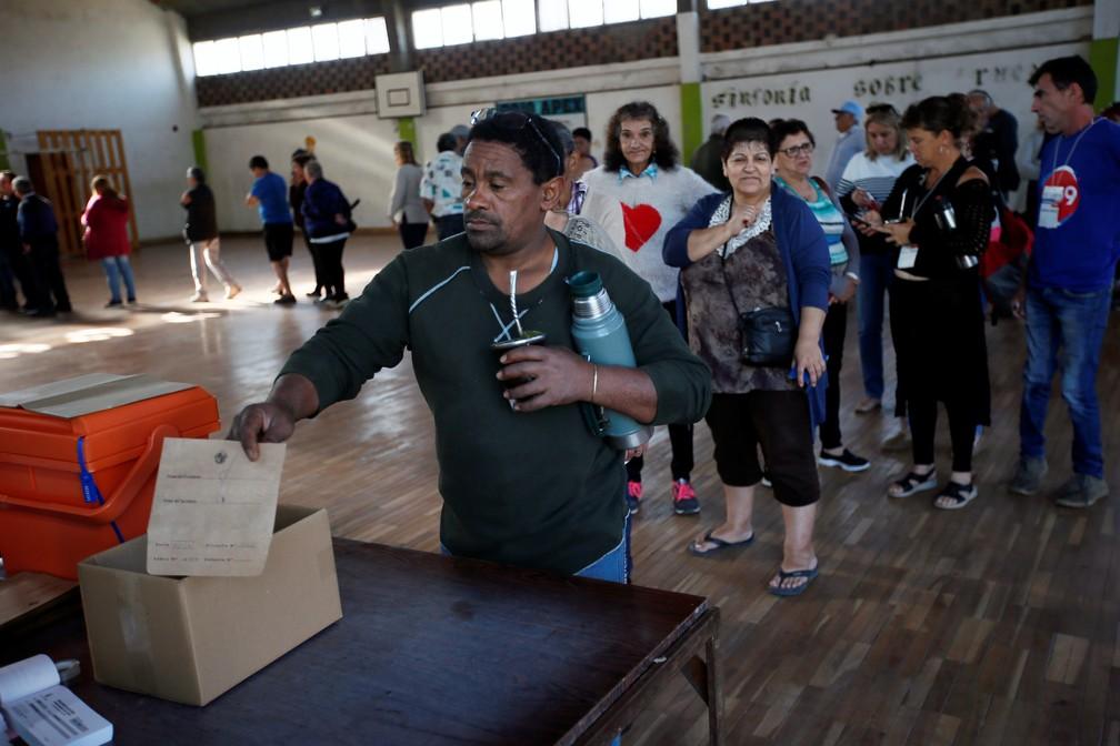 Eleitor entrega documento para votar em Montevidéu neste domingo (24). — Foto: Mariana Greif/Reuters