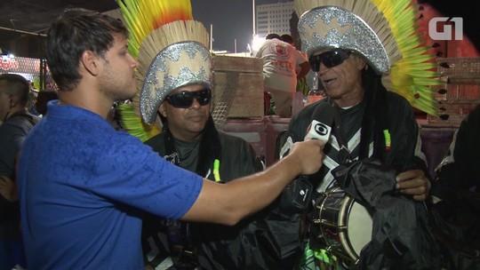 Integrantes da bateria da Grande Rio protegem instrumento da chuva