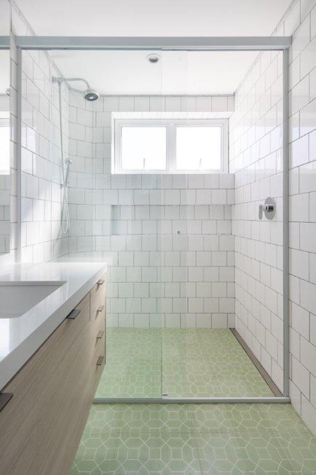 No banheiro da suíte, o ladriho verde-claro cria uma paleta suave ao lado dos azulejos brancos destacados pelo rejunte escuro. Materiais das antigas com roupagem moderna (Foto: Alexandre Disaro/Divulgação)