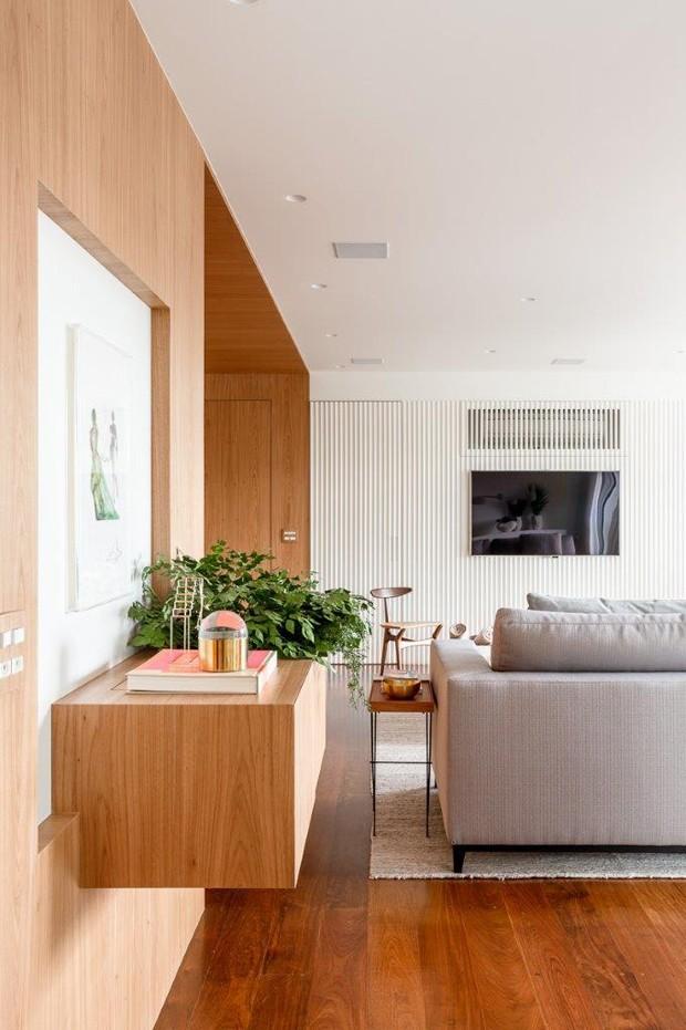 Painel de madeira é o ponto forte do projeto deste apartamento (Foto: Ricardo Bassetti )