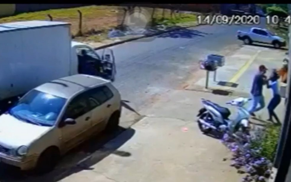 Homem bate a mulher contra o portão, acertando a parte de trás da cabeça dela — Foto: Reprodução/TV Anhanguera