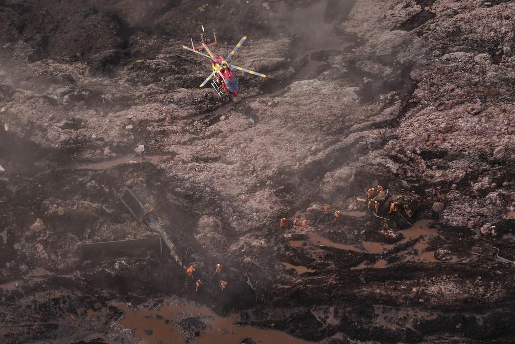 25 de janeiro - Helicóptero sobrevoa bombeiros que trabalham no resgate após rompimento da barragem em Brumadinho — Foto: Douglas Magno/AFP