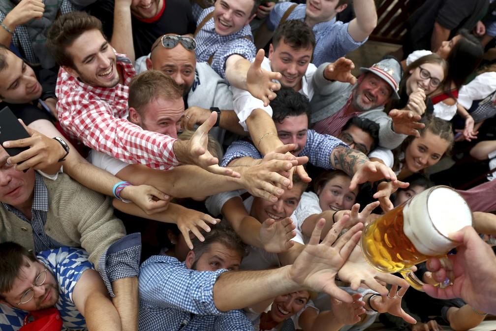 Foto de 21 de setembro de 2019 mostra pessoas disputando um caneco de cerveja durante a abertura da 186ª Oktoberfest em Munique, na Alemanha. Autoridades bávaras anunciaram em 3 de maio de 2021 que o festival da cerveja será cancelado pelo 2º ano consecutivo devido à pandemia do novo coronavírus — Foto: Matthias Schrader/AP