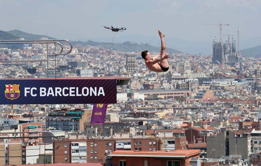 ff91b0cb87 Salto ornamental e drone com camisa gigante ao lado da Sagrada Família ao  fundo no lançamento
