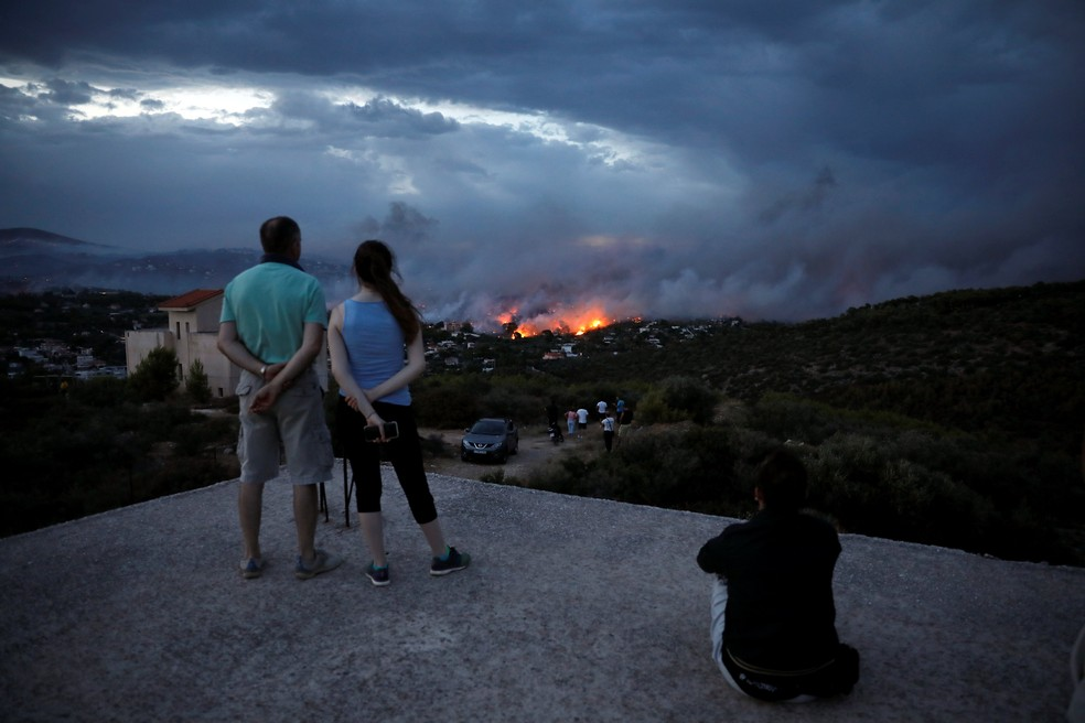 Pessoas assistem a incêndio em Rafina, na Grécia (Foto: Reuters/Alkis Konstantinidis)