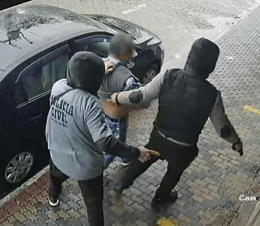 Momento em que bandidos levar dono da sorveteria até o carro — Foto: Divulgação/Polícia Civil