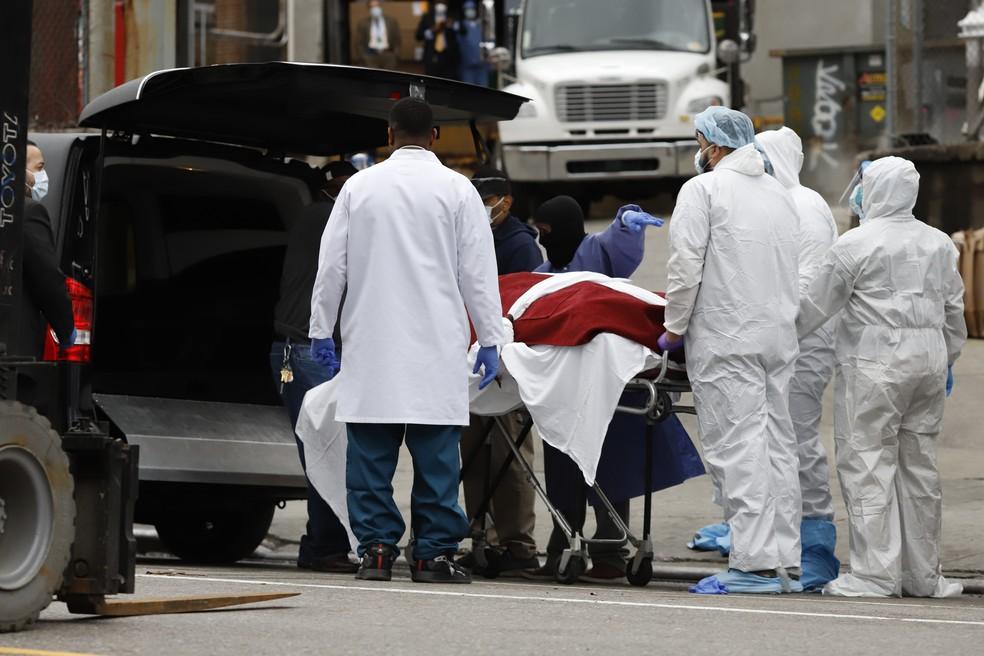 Em Nova York. profissionais de saúde colocam uma vítima da Covid-19 em um carro — Foto: Stefan Jeremiah / Reuters