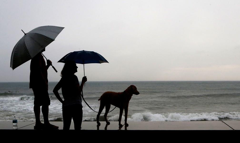Casal e cão aguardam a chegada do furacão Willa, em Mazatlan, no México, na terça-feira (23)  — Foto: Marco Ugarte/AP