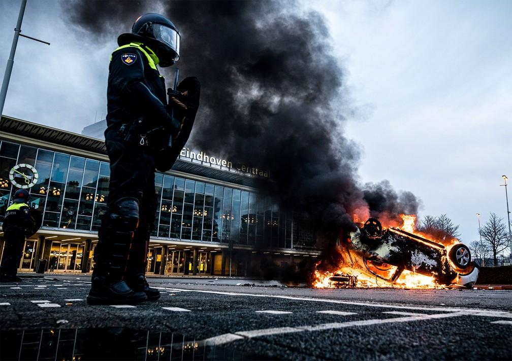 Carro foi incendiado em frente a estação ferroviária durante protesto em Eindhoven contra toque de recolher na Holanda — Foto: Rob Engelaar/ANP via AFP