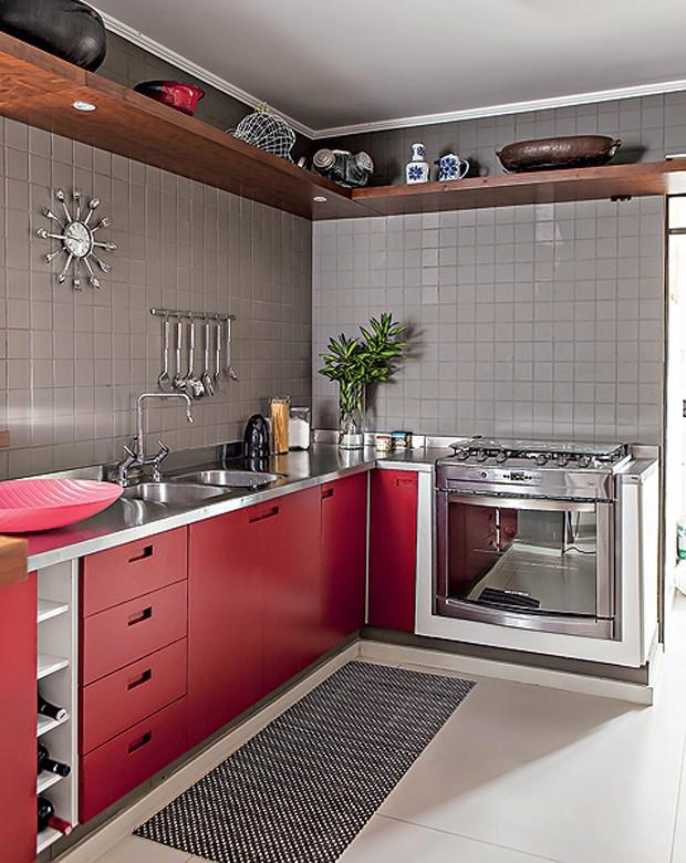 A cozinha projetada pelo arquiteto Gustavo Calazans segue o mesmo estilo do resto da decoração. Há, inclusive, a mesma prateleira de imbuia no alto, que guarda panelas e outros acessórios que não são usados no dia a dia (Foto: Edu Castello/Casa e Jardim)