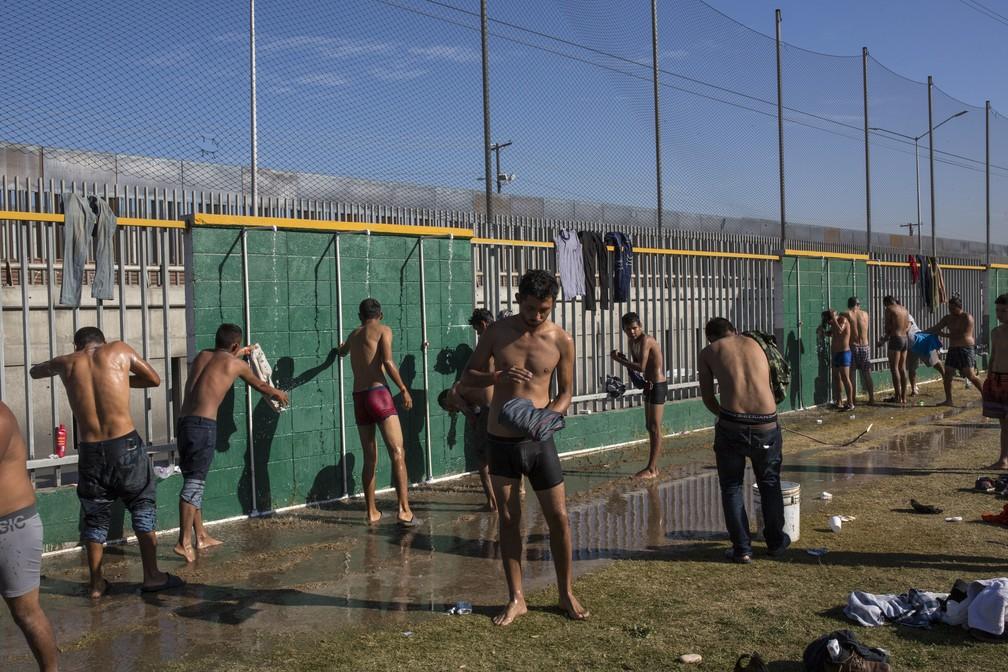 Imigrantes da caravana da América Central tomam banho em abrigo temporário em Tijuana, no México — Foto: Rodrigo Abd/AP Photo