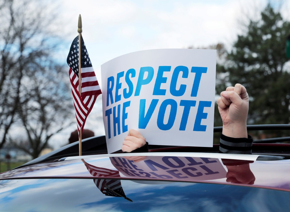 Apoiador de Biden mostra cartaz em Michigan, estado que certificou vitória nesta segunda-feira (23) — Foto: Reuters/Rebecca Cook